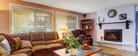 Modernized living room with couch and recliner, and fireplace. Stock Photo