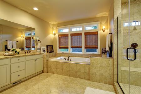 Baño principal con piso de baldosas, bañera y espejo de cuerpo entero. Foto de archivo
