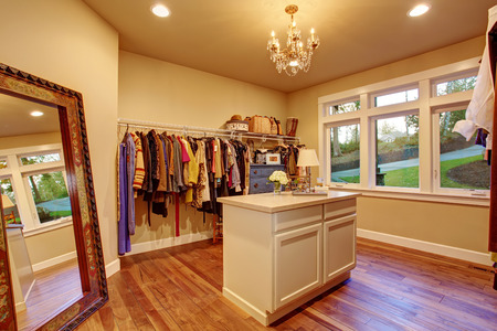 Large walk in closet with hardwood floor and an island.