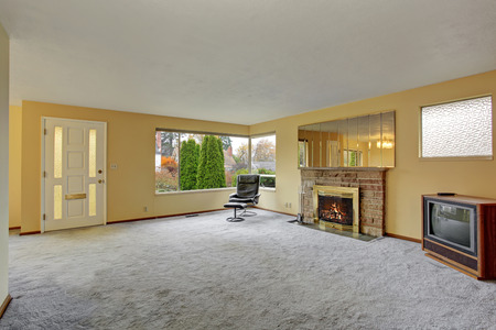 family  room: Simple living room with carpet and windows. Stock Photo