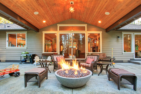 lands: Large back yard with grass and covered patio with firepit.