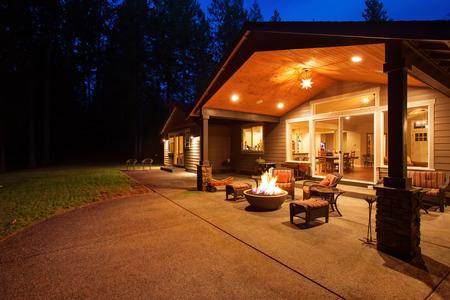 Großen Hinterhof mit Gras und überdachte Terrasse mit Feuerstelle.