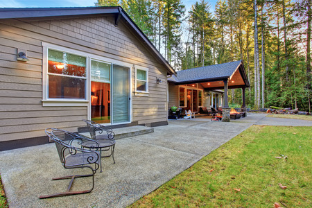 outside: Large back yard with grass and covered patio with firepit.