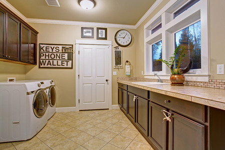 interior designer: Nice laundry room with tile floor, washer, dryer, and windows.