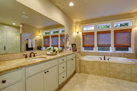 bathroom mirror: Large master bathroom with tile floor, bathtub, and long mirror.