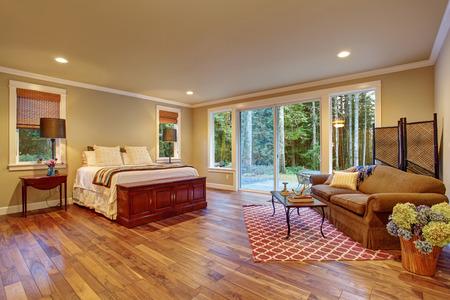 Großes Schlafzimmer mit Holzboden und Glas-Schiebe-Tür zum Hinterhof.