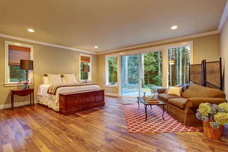 Large master bedroom with hardwood floor and sliding glass door to backyard.