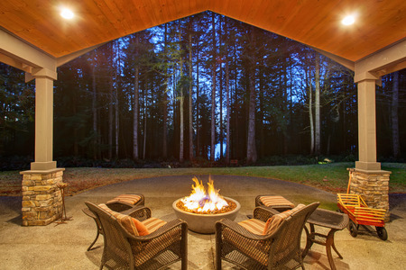 comfortable cozy: Large back yard with grass and covered patio with firepit.