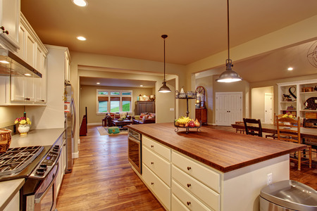 white wood floor: Classic kitchen with hardwood floor, an island, and connected dinning room and living room. Stock Photo