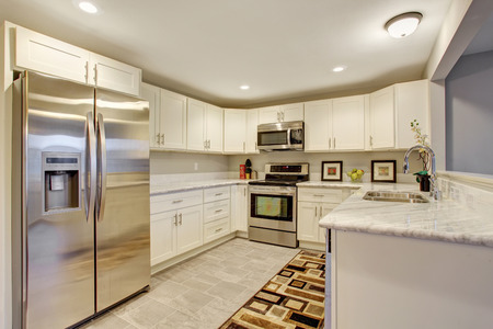 ceiling tile: Bright kitchen with marble counters, and tile floor.