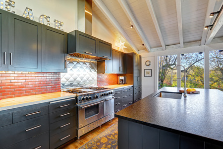 comfortable home: Luxury beautiful dark modern kitchen with vaulted wood ceiling, hardwood floor and huge stove.