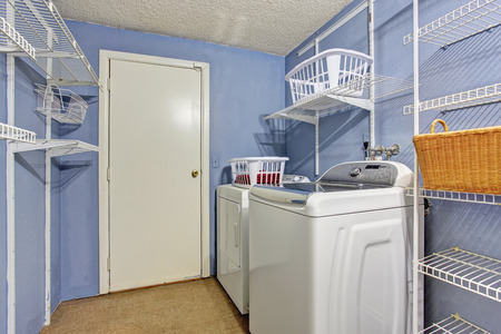 Small laundry room with periwinkle walls and washer and dryer.