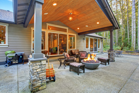 back yard: Large back yard with grass and covered patio with firepit.