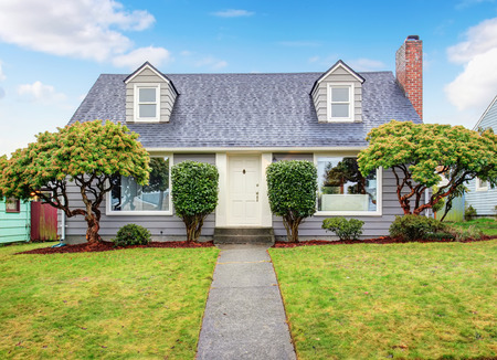 front house: Authentic gray house with large lawn and trees.