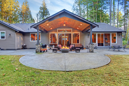 Large back yard with grass and covered patio with firepit.