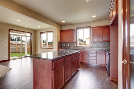 cabinets: Traditional kitchen with dark hardwood floor, island, and stained cabinets, in luxurious northwest home.