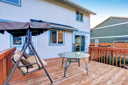 grande terrasse en bois avec balancer banc et table en verre.