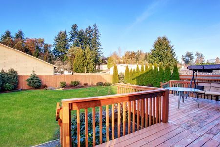back yard: Large back yard with wood deck, including swinging bench, and lots of grass.