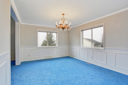 Spacious dinning room with blue carpet, and a beautiful chandelier. Stock Photo
