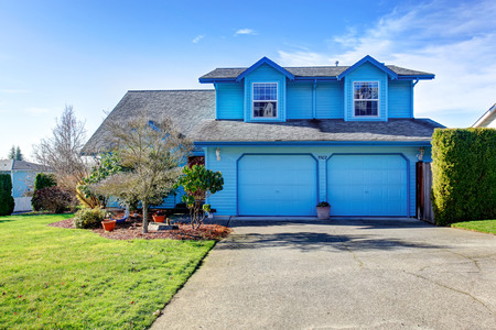 garage on house: Large bright blue house with driveway and garage.