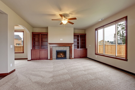 Lovely unfurnished living room with stained wood cabinets and fireplace.