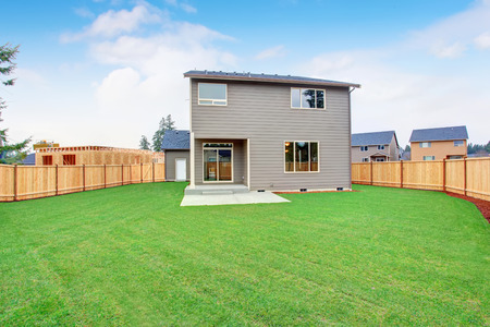 Large back yard with patio and lots of grass.