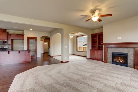 Lovely unfurnished living room with carpet and fireplace.