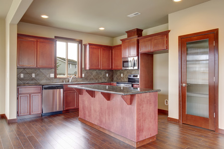 kitchen cabinets: Traditional kitchen with dark hardwood floor, island and stained cabinets, in luxurious northwest home. Stock Photo