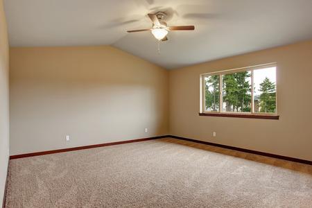 Large master bedroom with carpet, dark wood trim and three piece window. Stock Photo