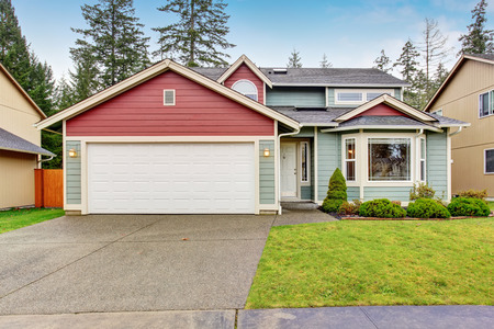 front yard: Classic house with garage, driveway and grassy front yard. Stock Photo