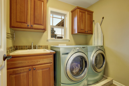타일 바닥과 가전 제품이있는 간단한 세탁실.