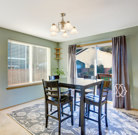 Well put together dinning room with sliding glass door, window and modern decor rug.