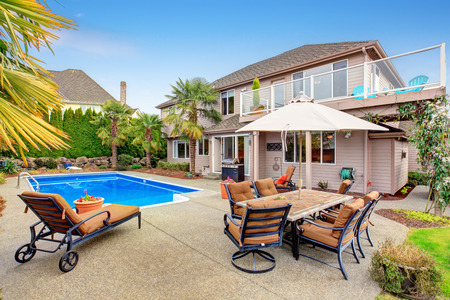 Luxurious northwest home with large pool and covered seating area. Stock Photo