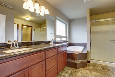 Large elegant master bathroom with tile floor, marble counters, including an excellent tub and shower.