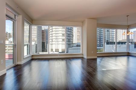 Große leere Wohnzimmer mit Kamin und Parkettboden.