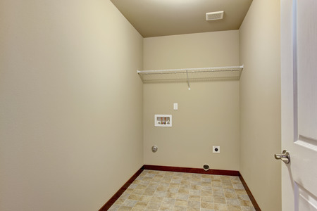 unfurnished: Small unfurnished laundry room with tile floor.