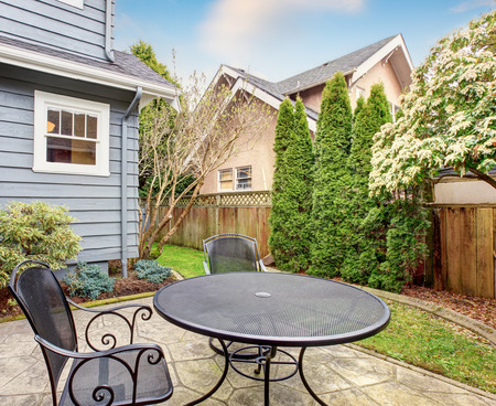 back yard: Small furnished back yard with patio and greenery. Stock Photo