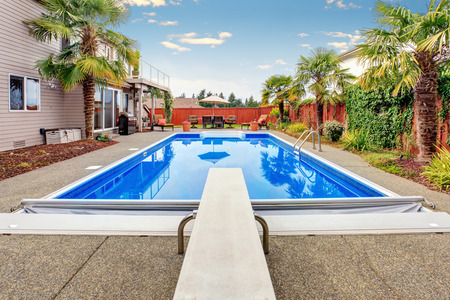 pool deck: Luxurious northwest home with large pool and covered seating area. Stock Photo