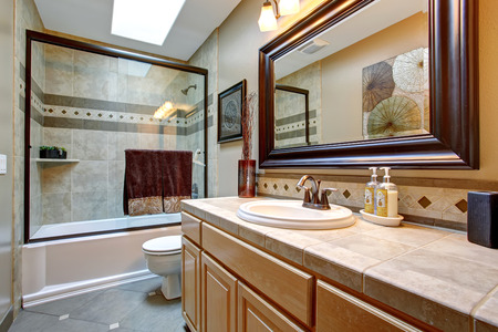 Elegant bathroom with glass shower, large framed mirror, and great decor.
