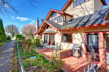 trims: Gorgeous tan northwest home with red trim and garden area.