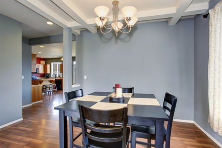 Simplistic dinning room with gray walls, and black table chair set.