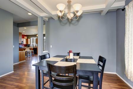 Zjednodušující jídelna s šedými zdmi, a černý stůl židle set.