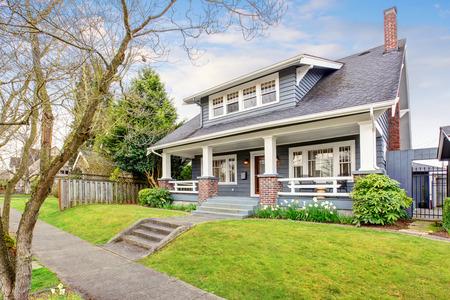 Modern noordwesten huis met witte versiering, en gras gevuld voortuin.