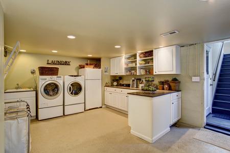 Große Waschküche mit Geräten und weißen Schränken.