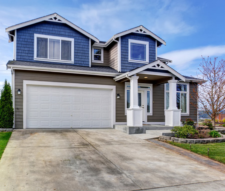 white trim: Large blue and gray home with white trim, also a driveway.