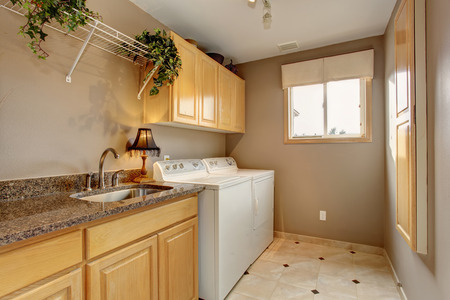 Traditional laundry room with tile floor, and washer dryer combo. Stock Photo