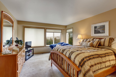 bed room: Large bedroom with stripped bedding and carpet.