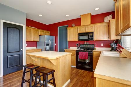 Kleine Küche mit Insel, auch rote und graue Wände.