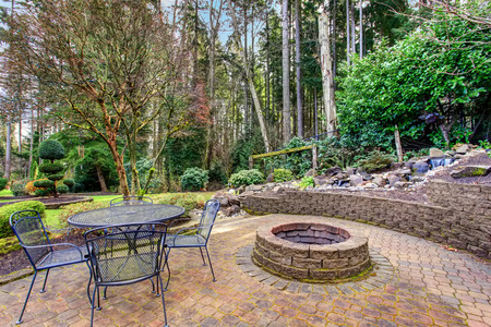 Vintage back patio with fire pit, furniture, and lots of greenery. Imagens