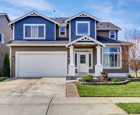 driveways: Large blue and gray home with white trim, also a driveway.